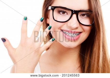 Vision and dentistry problems concept. Happy nerdy teenage wearing big eyeglasses showing her braces on teeth and painted nails.