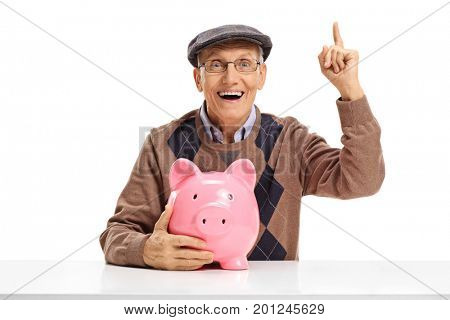 Cheerful senior with a piggybank seated at a table pointing up with his finger isolated on white background