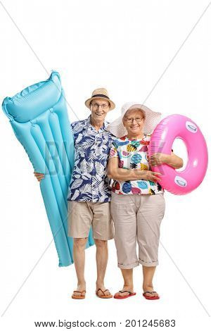 Full length portrait of seniors with an air mattress and a swimming tire isolated on white background