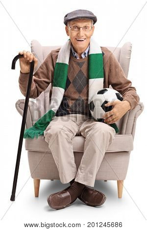 Elderly soccer fan with a football and a scarf sitting in an armchair isolated on white background