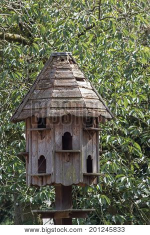 Traditional wooden dovecote. Free-standing dovecot. Weathered wood house for doves and pigeons.