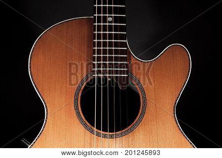 Acoustic guitar in close up. Roundback steel-strung folk guitar. Modern stringed instrument.