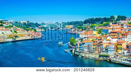 Beautiful panoramic view over Dom Luis I bridge and traditional boats on Rio Douro river, in Porto, Portugal