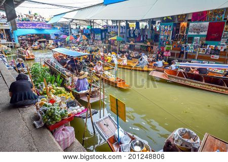 Bangkok, Thailand - August 08, 2017: Traditional vendors on the famous floating market Damnoen Saduak in Bangkok. Local people selling goods on the wooden boats at Damnoen Saduak floating market.