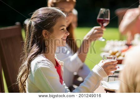 leisure, holidays and people concept - happy girl eating with family at festive dinner or summer garden party