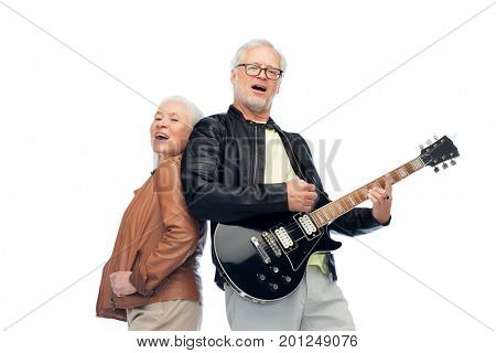 music, age and people concept - happy senior couple with electric guitar singing