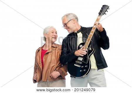 music, age and people concept - happy senior couple with electric guitar