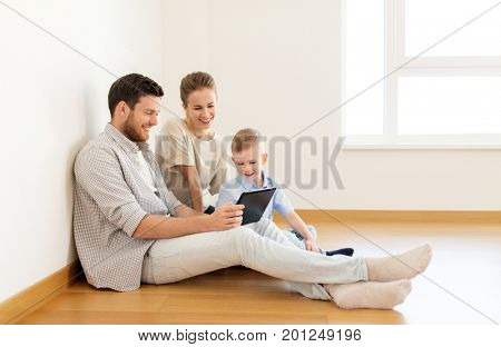 mortgage, people, housing and real estate concept - happy family with tablet pc computer moving to new home