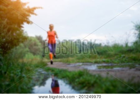 Blurred photo of sportswoman running along path in park