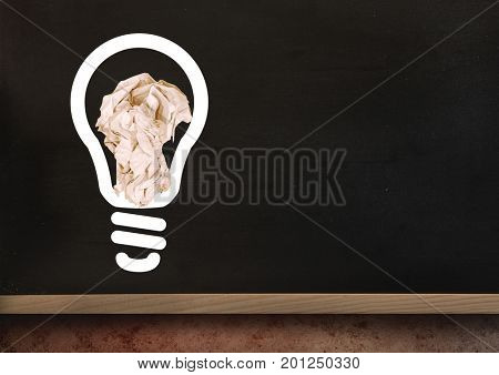 Digital composite of light bulb with crumpled paper ball in front of blackboard