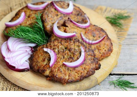 Chicken liver patties with carrot and onion. Homemade fried chicken liver patties on a wooden cutting board. Easy chicken liver cakes recipe. Closeup
