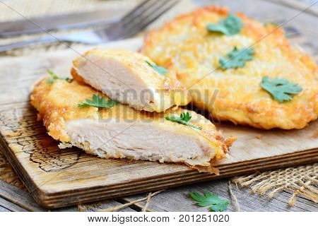 Chicken steaks fried in egg batter. Crispy chicken steaks on a wooden board. Easy chicken breast recipe for dinner. Closeup