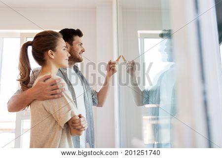 mortgage, people and real estate concept - happy couple looking through window at new home