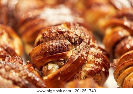 food, cooking and baking concept - close up of buns or pies at bakery