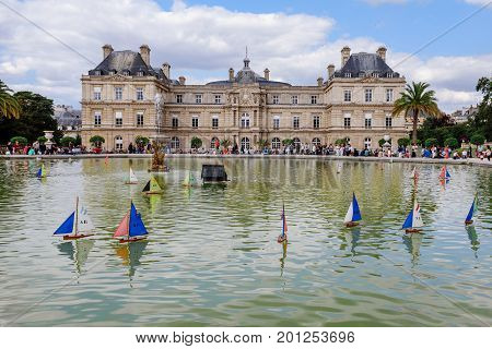 Paris, France - August 13, 2017. Luxembourg Palace building reflected in the fountain pond with children sail boats in Luxembourg Garden public park. Seat of french senate.