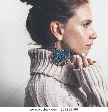 Boho jewelry on model: ethnic stone rings and earrings. Beautiful woman wearing warm woolen sweater and fashion jewellery. Minimal style and pastel tone.
