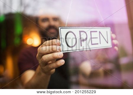 small business, people and service concept - man with open word on banner at bar or restaurant window