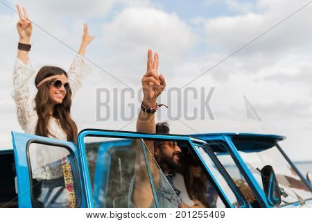 summer holidays, road trip, travel and people concept - smiling young hippie friends at minivan car showing peace hand sign