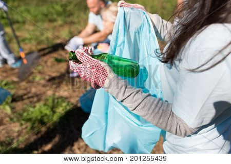 volunteering, people and ecology concept - volunteer woman with garbage bag and glass bottle cleaning area in park