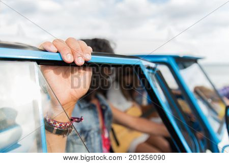 summer holidays, road trip, travel and people concept - close up of hippie friends at minivan car