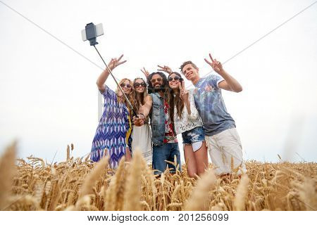 summer, technology and people concept - smiling young hippie friends in sunglasses taking picture by smartphone selfie stick and showing peace sign on cereal field