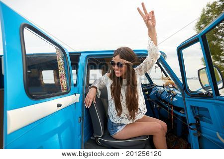summer holidays, road trip, travel and people concept - smiling young hippie woman showing peace gesture in minivan car
