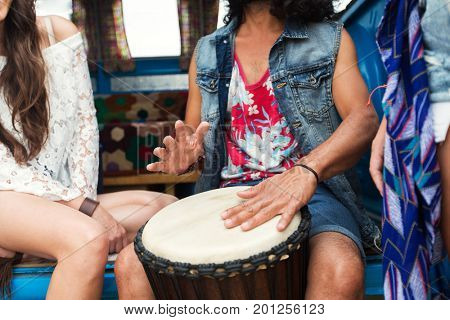 summer holidays, music, travel and people concept - close up of hippie friends having fun and playing tom-tom drum over minivan car
