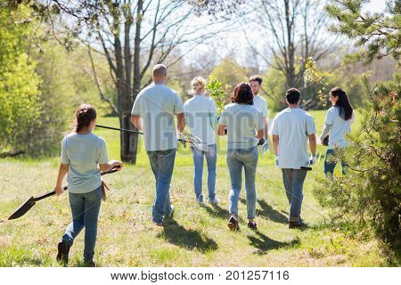 volunteering, charity, people and ecology concept - group of happy volunteers with tree seedlings and garden tools walking in park