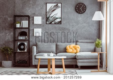 Black Clock Above Grey Settee