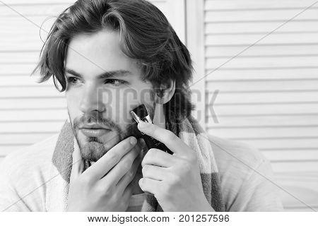 Man Holds Razor And Starts Shaving His Beard