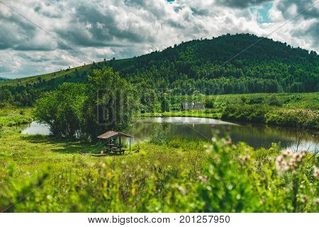 Summer landscape with small lake of fresh water hills with forests in distance green meadows of native grasses arbour with trees near submerged country house Altai mountains Aya district Russia