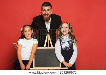 Schoolgirls stand near blackboard. Girls in school uniform on red background. Studying and back to school concept. Man with beard and happy face stands with children with big schoolbags copy space.