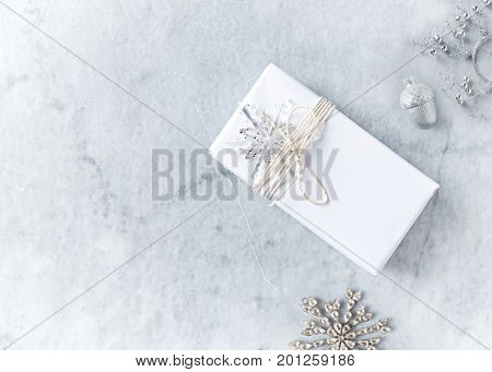 Christmas present wrapped in white paper on gray marble background