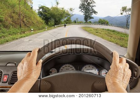 Senior woman driving a car slowly on mountain road.