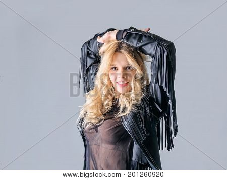 Young woman in a black leather rocker jacket. Girl posing on camera in black cowboy jacket. Model blonde posing in sexy clothes