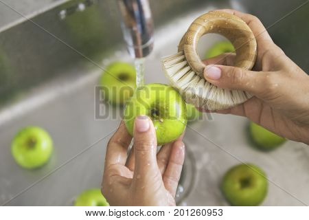 Young Vegan Girl Washing Green Apples with Bamboo Brush. Hand Holding Fresh Fruits Under Running Water in Kitchen Sink. Healthy Lifestyle Hygiene Concept