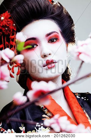 young pretty geisha in kimono with sakura and red decoration design on white background close up
