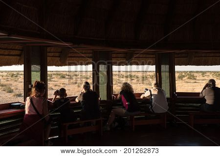 ETOSHA NATIONAL PARK NAMIBIA - JUNE 26 2017: Unidentified tourists in the upper level of the hide at the waterhole at the Olifantsrus Rest Camp in the Etosha National Park