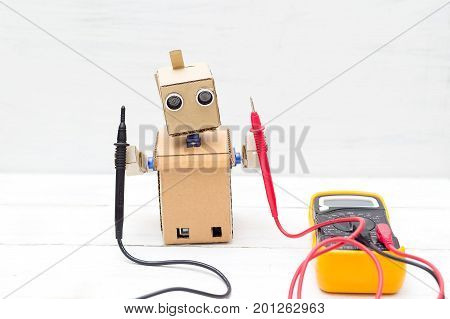 Robot holds voltmeter. horizontal photo. artificial intelligence
