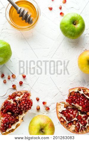 Frame of grains of pomegranate, honey and apples on a white background vertical