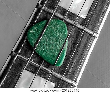 green guitar pick in fingerboard. pick is beetween strings.