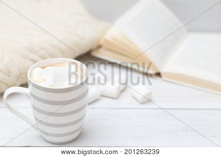 Cup of hot chocolate with marshmallows on a white wooden background. Mock up