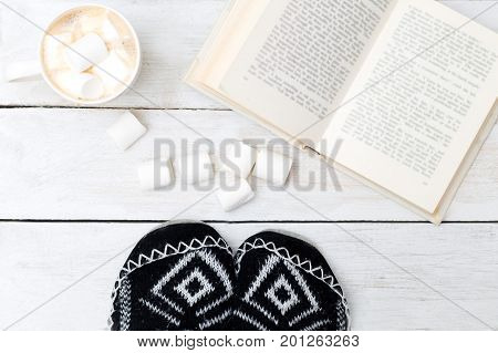 Coffee cup with cream and marshmallows open book. Concept cozy home sweet home