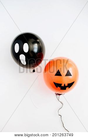Halloween minimal concept. Two balloons with funny smiling and scary faces on white background. Flat lay top view.