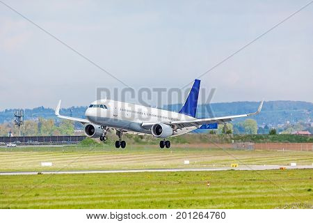Airplane with blue tail fin on landing approach at airport - runway and green meadow in front