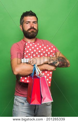 Man in pink tshirt holds big box and shopping bags on green background. Guy with beard and serious face does shopping. Macho guy holds pink packets. Shopping and sale concept