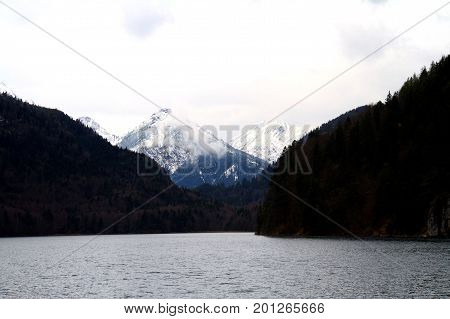 A snow covered peak in the German Alps with a lake in the foreground.
