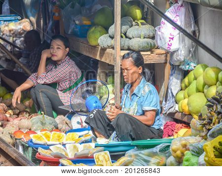 Samut Songkhram Province, Thailand - August 24, 2017: People are picked up the food for dodge the train are traveling across the market in Maeklong market,Thailand.