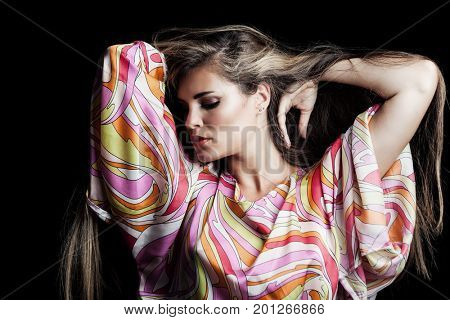 beauty portrait of blonde girl with long hair in silky colorful dress studio shot