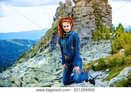 beautiful brunette girl in black clothes posing on a huge rock among stones